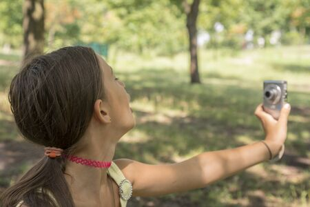 Little cute girl holding camera in hand and take a picture with selfie shot in park. beautiful eight-year-old girl in the park doing selfie. Stock Photo - 131849247