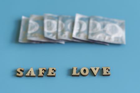 the concept of safe sex. inscription safe love. Condoms on a blue background.