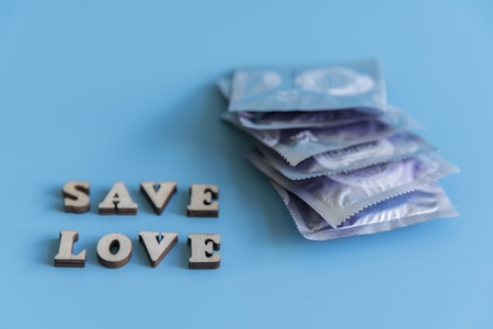 the concept of safe sex. inscription safe love. Condoms on a blue background. Stock Photo