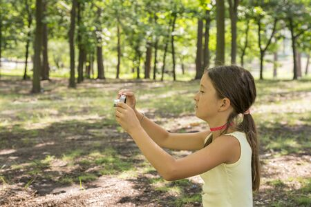 Little girl child of 8 years looking at camera sitting on green lawn in city park. girl 8 years in the park taking pictures of nature.