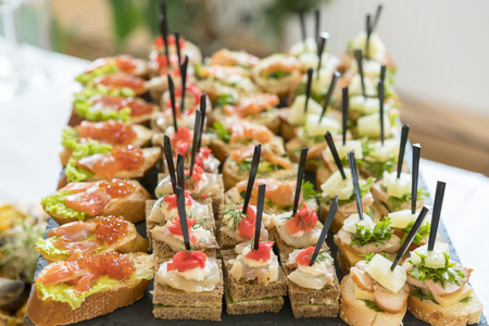 Crostini with different toppings on wooden background. Delicious appetizers. Front view. Gourmet appetizers: caviar, venison, tuna and salmon.