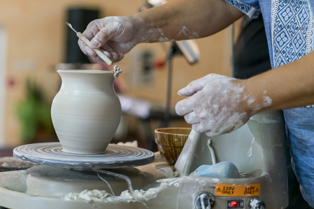 Creating a jar or vase of white clay close-up. Master crock. Man hands making clay jug macro. The sculptor in the workshop makes a jug out of earthenware closeup. Twisted potter's wheel