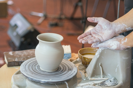 the Potter molds a pot from clay on a Potter's wheel. The master's hands make a pot on the potter's wheel Stock fotó