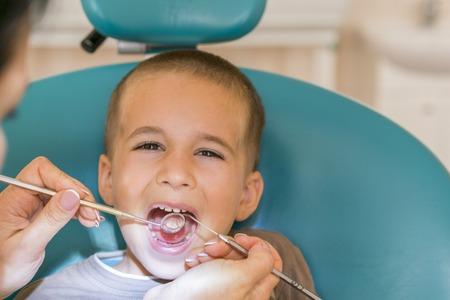 Pediatric dentist examining a little boys teeth in the dentists chair at the dental clinic. Dentist examining little boy's teeth in clinic.