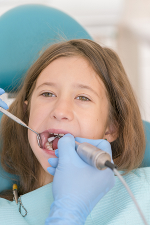 Macro close up of young child with open mouth at dentist. Teeth checkup at dentist's office. Dentist examining girls teeth in the dentists chair. vertical photo.