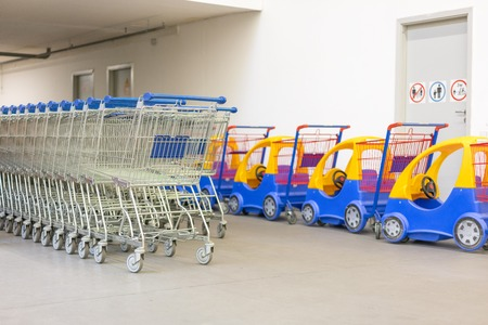 Shopping Trolleys - Supermarket Shopping Theme. Row of shopping carts with blue handles and childrens carts Stock Photo