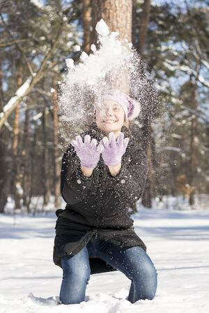 Girl throws snow up. Portrait of the beautiful girl throwing snow in the winter. Happy young woman plays with a snow in sunny winter day. vertical photo.