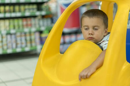 Baby sleeping in a trolley in a supermarket. Sleeping boy is in the chair on the trolley in the supermarket