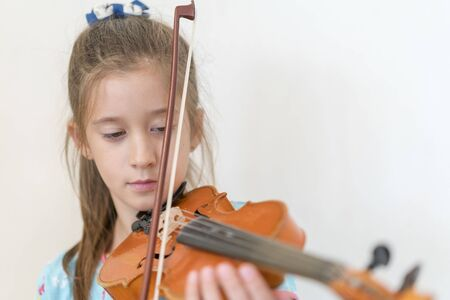 Portrait of a young blond teenage girl playing violin. Girl playing the violin. Stok Fotoğraf