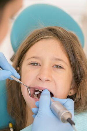 Macro close up of young child with open mouth at dentist. Teeth checkup at dentists office. Dentist examining girls teeth in the dentists chair. vertical photo.