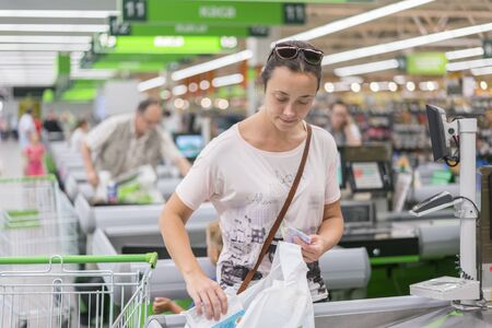 A middle-aged woman at the checkout in the supermarket. The woman counts on the checkout in the supermarket Stock fotó