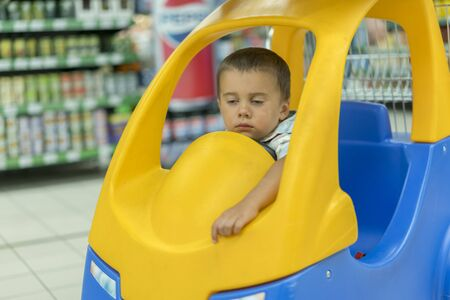 Kid is bored in the store. Sleeping boy is in the chair on the trolley in the supermarket Stockfoto