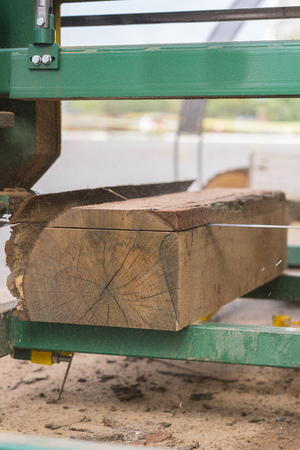 Sawmill. Process of machining logs in equipment sawmill machine saw saws the tree trunk on the plank boards. Wood sawdust work sawing timber wood wooden woodworking. vertical photo Banco de Imagens