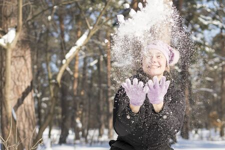 Girl throws snow up. Portrait of the beautiful girl throwing snow in the winter. Happy young woman plays with a snow in sunny winter day.