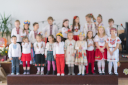 children perform at concert in primary school. Childrens theatrical creativity, amateur performance in Kindergarten. Childrens creativity. Childrens choir in kindergarten. Blurry. Stock Photo