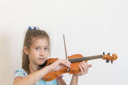 Lindo alumno tocando el violín en el aula de la escuela primaria. Niña tocando el violín. Foto de archivo