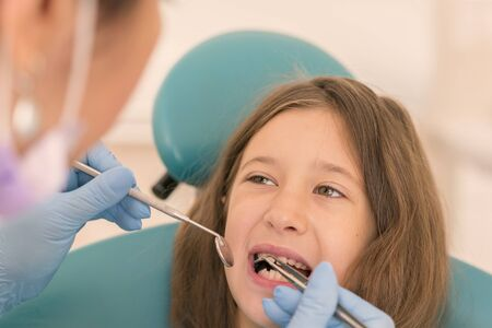Macro close up of young child with open mouth at dentist. Teeth checkup at dentists office. Dentist examining girls teeth in the dentists chair.