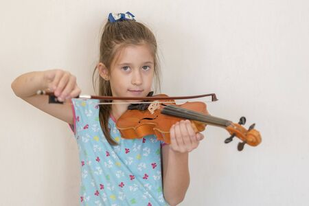 Cute pupil playing violin in classroom at the elementary school. Girl playing the violin. Stok Fotoğraf - 131849676