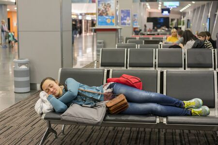 Young woman sleeping at the airport while waiting for her flight. Tired female traveler sleeping on the airpot departure gates bench with all her luggage by her side. Tireing travel concept 写真素材 - 129977271