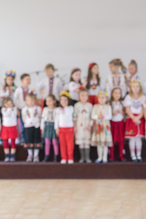 children perform at concert in primary school. Childrens theatrical creativity, amateur performance in Kindergarten. Childrens creativity. Childrens choir in kindergarten. Blurry Stock Photo