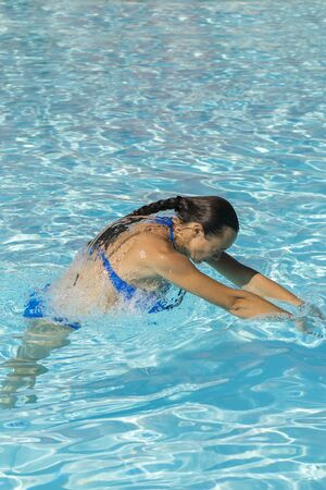 Woman diving in the swimming pool. Young beautiful girl swimming in pool. Brunette relaxing in clear warm water on sunny day. Top view Close up Slow motion. Vertical photo. Zdjęcie Seryjne