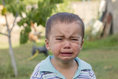 Crying little boy. Cry. Portrait of boy. Caucasian child looks at camera. Charming boy the kid cries with tears in his eyes. an angry temper. hysterics Фото со стока