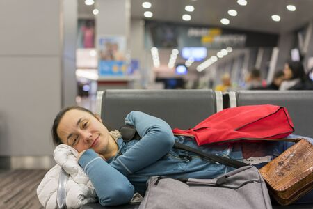 Young woman sleeping at the airport while waiting for her flight. Tired female traveler sleeping on the airpot departure gates bench with all her luggage by her side. Tireing travel concept. close up. 写真素材 - 129977350