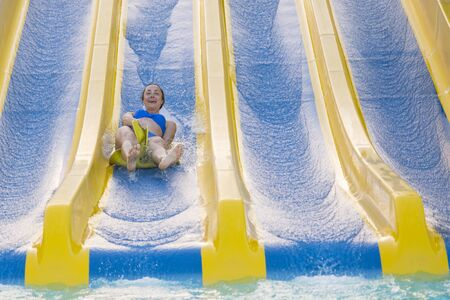 Fun in the sun-pretty girl in bikini comes down water chute in to swimming pool. Beautiful girl riding a water slide. happy woman going down on the rubber ring by the orange slide in the aqua park