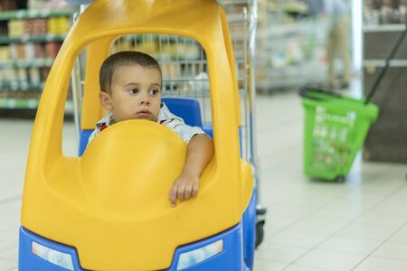 Cute sad little 2 year old baby boy child in the little toy-car trolley at supermarket, Dad or Parent pushing child shopping cart car with his son, Kid first experience concept