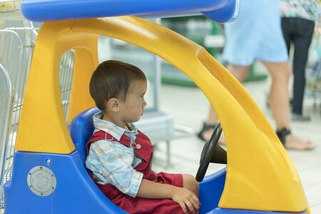 Cute little 2 year old baby boy child in the little toy-car trolley at supermarket, Dad or Parent pushing child shopping cart car with his son, Kid first experience concept