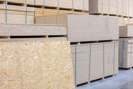 lumber osb, plywood, mdf, project panel at hardware store in USA. Wooden bars, flake board, sterlingboard on shelves inside lumber yard of home improvement retailer. Customer shopping. Фото со стока