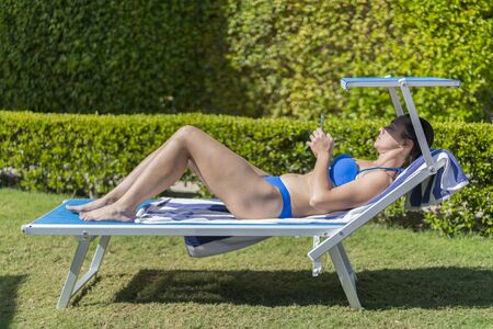 Summer lifestyle portrait of young stunning woman lying on the sunbed on the beach of the tropical island. Young white woman lying on blue sunbed. woman lying on a lounger in a green park. 版權商用圖片