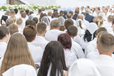 Men and women in white clothes prepare to receive water baptism