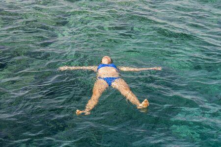 Young woman in bikini swimming in clear water. Woman swimmer swimming in blue sea. Woman swiming in the sea