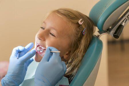 Little girl at the reception in the dentist's office. little girl sitting in a chair near a dentist after dental treatment. Little girl sitts in the dentist's office