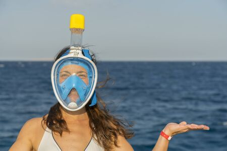 Funny young woman in a mask for swimming on the background of the sea. copy spase. close-up