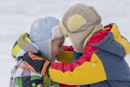 Two happy little brothers playing in the winter outside. Two happy little brothers in winter outside. two small boys in winter clothes Stok Fotoğraf