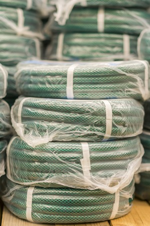 stacks of rolls yellow pvc plastic pipe on the counter in the store. Sale Hoses in the garden of various manufacturers, on shelves in store. Hose for watering in the store. vertical photo