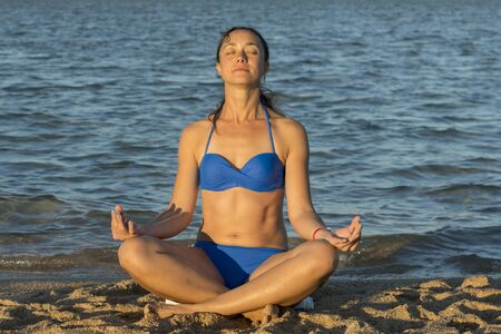 Young lady practicing yoga. Beautiful woman posing at sand beach. Workout near ocean sea coast. Fitness model caucasian ethnicity outdoors. Meditation. Healthy active lifestyle concept