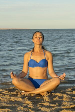 Young woman rests on the beach on a hot summer day. Young attractive smiling woman practicing yoga on a sea. Healthy active lifestyle concept