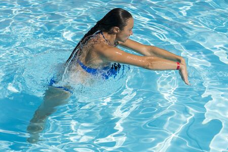 Woman diving in the swimming pool. Young beautiful girl swimming in pool. Brunette relaxing in clear warm water on sunny day. Top view Close up Slow motion Zdjęcie Seryjne