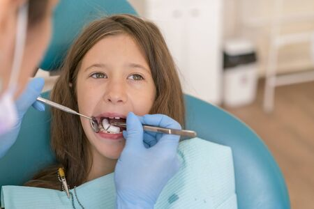 Teeth checkup at dentists office. Little girl at the reception in the dentists office. Little girl sitts in the dentists office