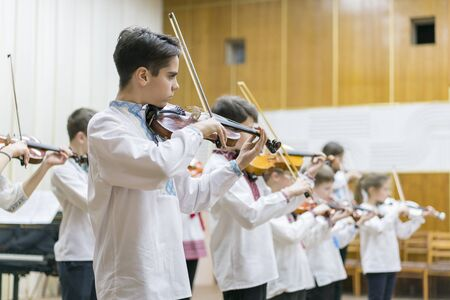 Kiev, Ukraine. January 21 2019 Childrens violin ensemble. Children with violins on stage. Childrens initiative, small talents. Early child development Sajtókép