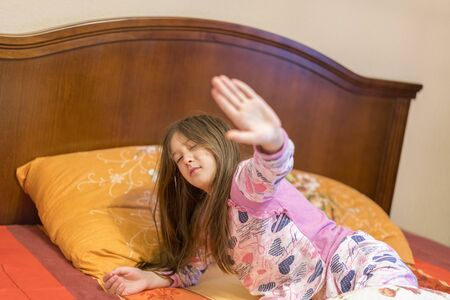 Cute little girl stretching her arms happily with a smile from waking up in her bed. child sleepy yawning in bed. Sleepy little girl on the bed