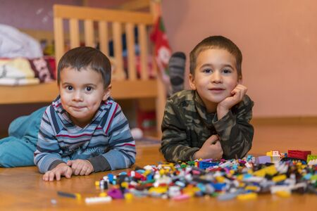 Two children playing with lots of colorful plastic blocks constructor sitting on a floor indoor. Two little brothers play constructor. Communication and friendship Stok Fotoğraf