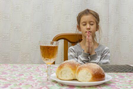 Child prays at Shabbat. Little Jewish Sabbath. Stock Photo