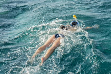 Young woman snorkeling in transparent shallow. Young woman at snorkeling in the tropical water. active woman free diving snorkeling in beautiful blue ocean on summer vacation.