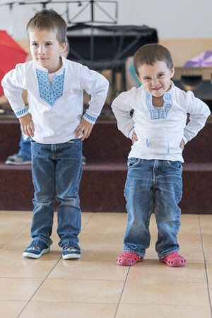 Two little boys perform on stage in kindergarten or school. performance of little boys.