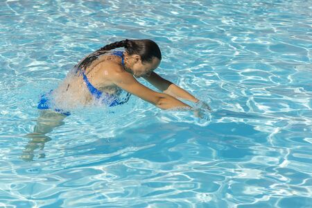 Woman diving in the swimming pool. Young beautiful girl swimming in pool. Brunette relaxing in clear warm water on sunny day. Top view Close up Slow motion Zdjęcie Seryjne - 129978202