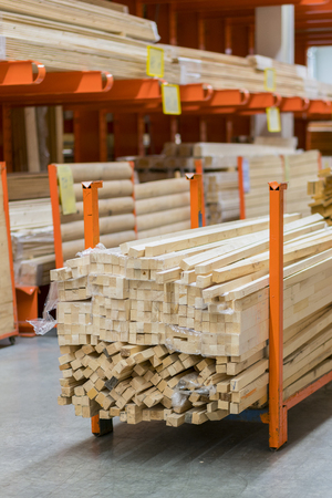 stack new wooden bars on shelves inside lumber yard of large hardware store in America. Rack of fresh mill or cut wood timber with flatbed cart and manual forklift in warehouse. vertical photo
